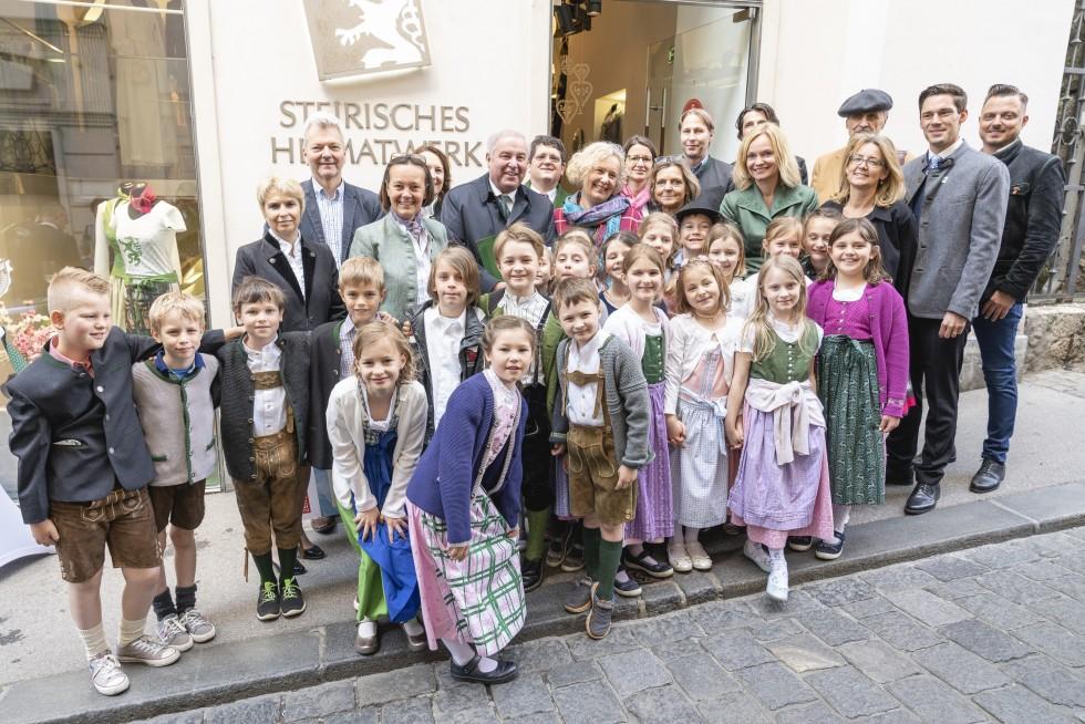 """Foto 2: Landeshauptmann Hermann Schützenhöfer mit VertreterInnen der volkskulturellen Verbände und Kindern der Volksschule Graz-St. Peter mit der neuen Publikation """"Wir leben Steiermark""""."""